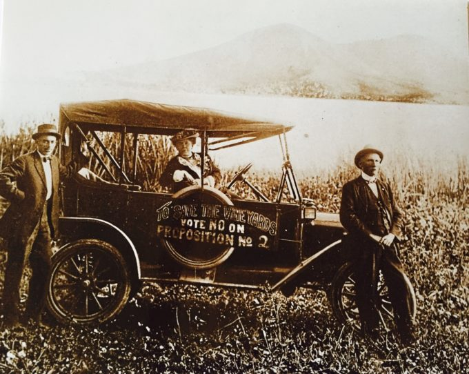 Historical figures and antique car in front of lake and mountains