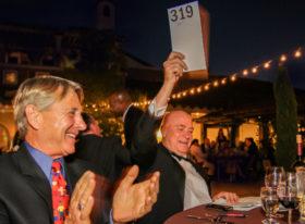 Auction participant raising his number to bid
